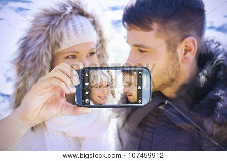 Hand holding smartphone showing against couple in fur hood jackets against snowed mountain