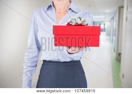 Businesswoman holding digital tablet against college hallway
