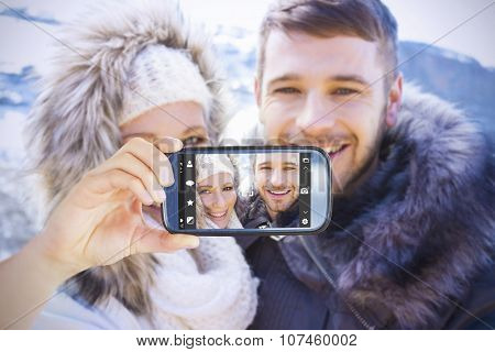 Hand holding smartphone showing against loving couple in jackets against snowed mountain
