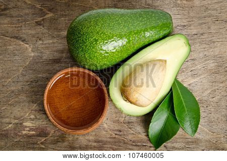 Fresh Avocado With Avocado Oil In The Wooden Bowl Isolated On Wooden Background
