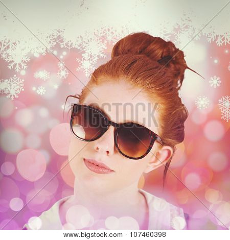 Hipster redhead wearing large sunglasses against snowflake pattern