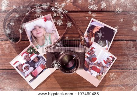 Girl wearing Santa hat at home against instant photos on wooden floor
