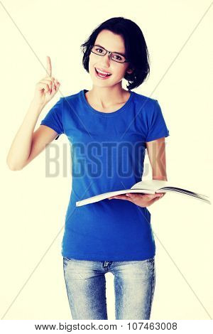 Studying happy young woman reading her notebook for school and pointing on copy space.
