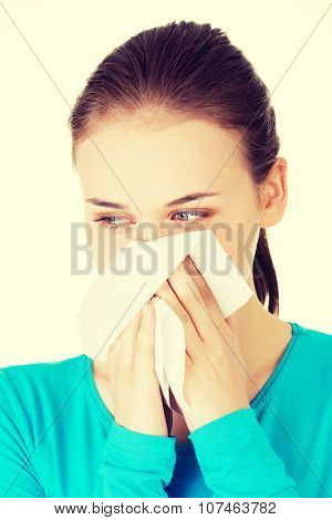 Young woman with tissue - sneezing. Allergy or cold.
