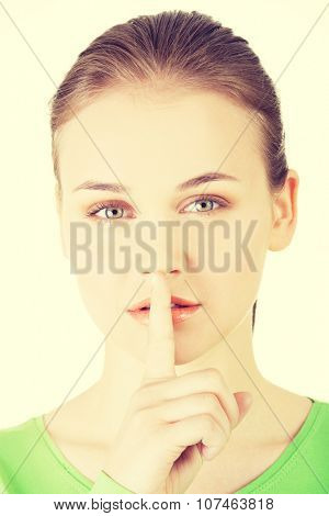 Hush be quiet woman. Teen girl with finger on her lips.