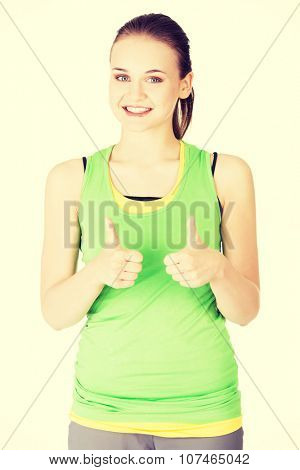 Attractive fitness woman in sport clothes gesturing thumbs up