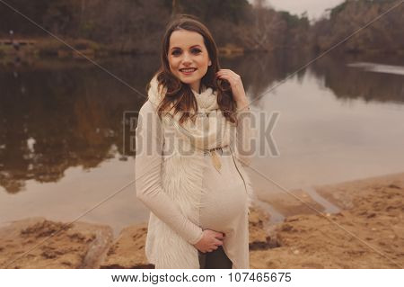 young beautiful pregnant woman on cozy warm walk on autumn riverside, warm toned, soft focus