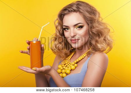 Girl With Blond Curly Hair  With Bijou, Holding Orange Bottle Of Beverage