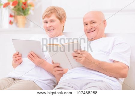 Pleasant adult couple lying on bed