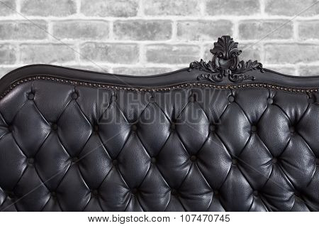 Black leather backrest background and concrete wall