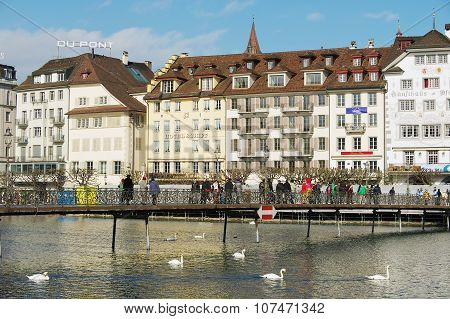 People walk by the bridge in Lucerne, Switzerland.