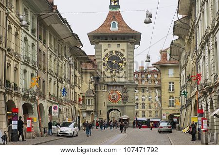People walk by the street with the historic Bern Clock tower at the background in Bern, Switzerland.