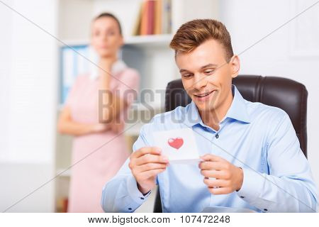 Male executive looks delighted while reading the note.
