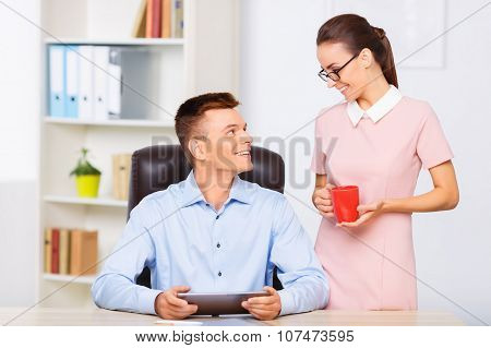 Coworker brings a cup of drink to her partner.