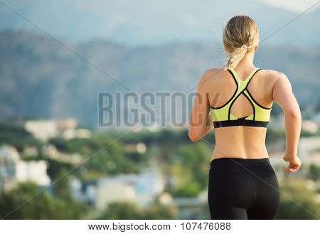 Young Woman Running Outdoors. Back View.