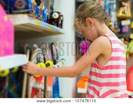 Little Girl Selecting Skateboard In Supermarket.
