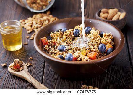 Healthy breakfast. Fresh granola, muesli with berries, honey and milk