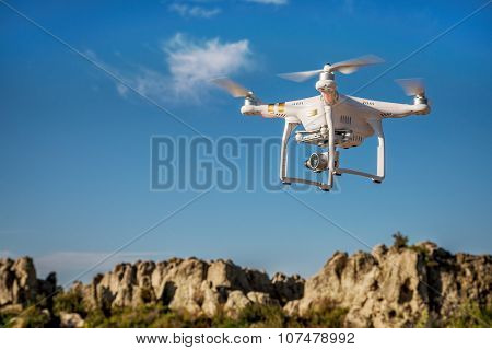 CARR, CO, USA, SEPTEMBER 14, 2015:  Radio controlled Phantom 3 quadcopter drone is flying with a camera over rock outcroppings of Natural Fort in northern Colorado,