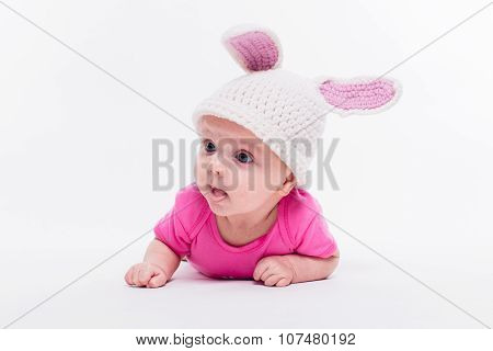 Cute Baby Girl Lying In A Bright Red T-shirt On A White Background Wearing A Hat In The Form Of A