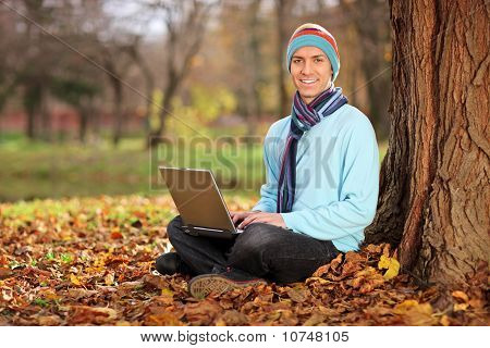 Young Man With Hat And Scarf Working On Laptop