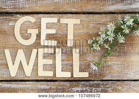 Get well written with wooden letters on rustic wooden surface and fresh chamomile flowers