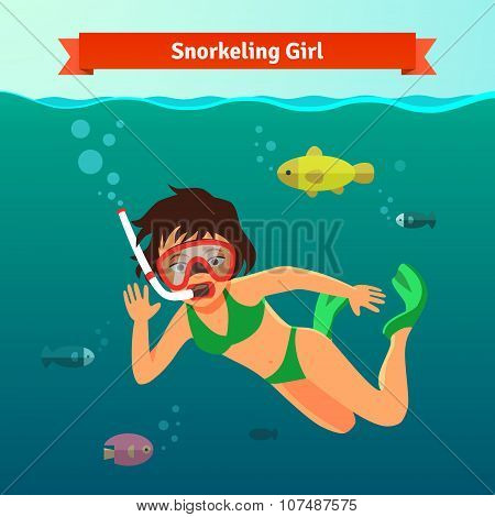 Girl snorkelling in the sea with fishes