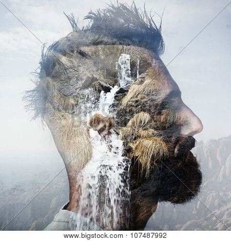 Double exposure portrait of  man with mohawk and a mountain