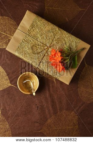A gift pack beautifully wrapped with golden paper and string. Tiny flowers placed on it along with Indian traditional lamp. View from above.