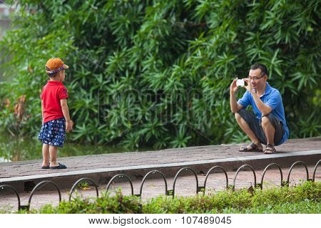 Asian little boy posing while his father taking photo of him