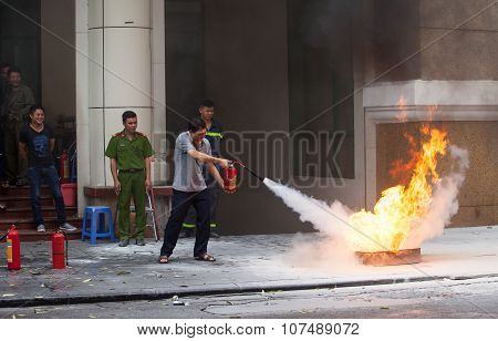 Asian civilian practicing to use fire extinguisher to rescue a fire