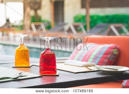 Red And Yellow Glass Of Water On Luxury Table Setting Near Swimming Pool, Selective Focus With Bokeh
