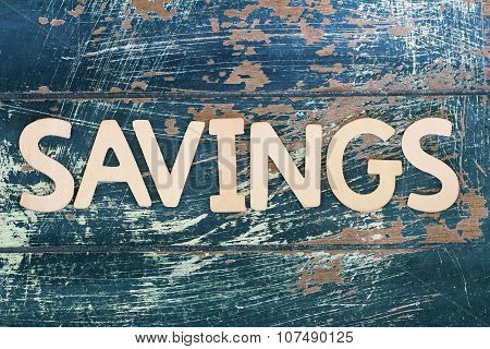 Word savings written on rustic wooden surface