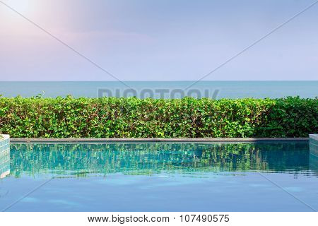 Swimming Pool With Ocean And Sunlight In Background