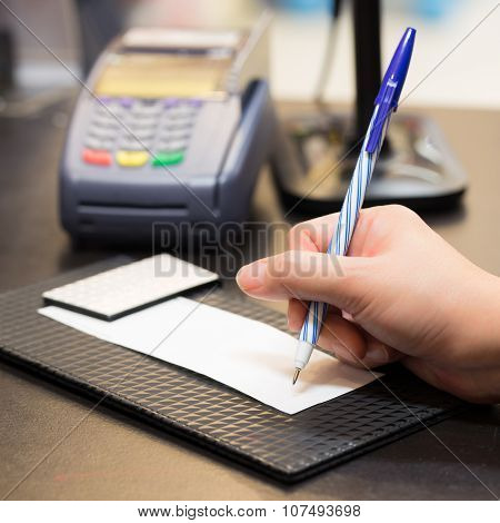 Consumer Signing On A Sale Transaction Receipt With Credit Card Machine And Barcode Scanner In Backg