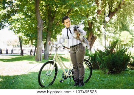 Young Woman With Dog And Bicycle In The Park