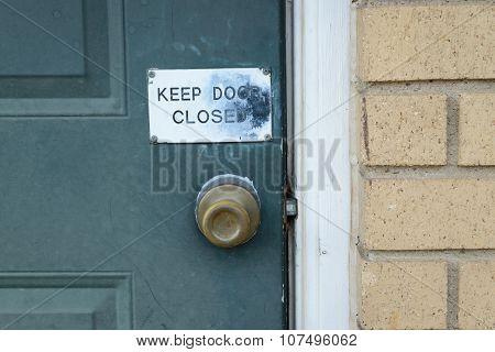 Green Door With Keep Door Closed Sign