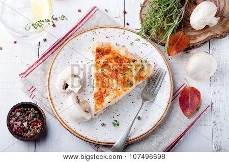 Mushroom, champignon pie, quiche slice on a ceramic plate