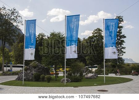KOENIGSSEE, GERMANY - AUGUST 13, 2015: Flags at the entrance to the Koenigssee are waving in the wind and are showing an advertisment of the Berchtesgadener Land region