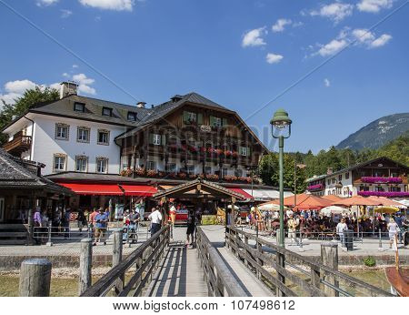 KOENIGSSEE, GERMANY - AUGUST 13, 2015: Pleasure boat at the landing stage of Schoenau where the boat trips on the Koenigsseet start historic buildings including the Hotel Schiffmeister are in the background