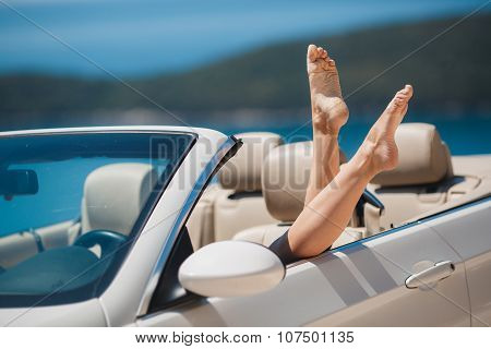 Slender women's legs look out of car window