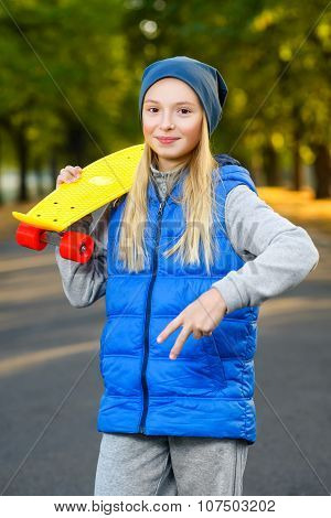 Smiling girl holding color plastic penny board or skateboards outdoor