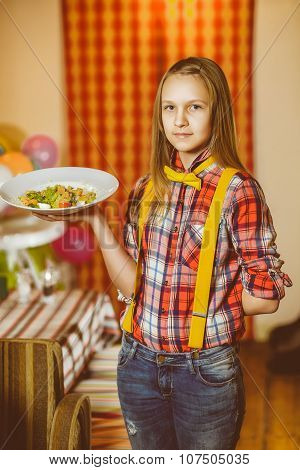 Happy cute smiling girl waiter holding a plate with salad