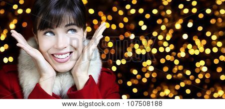 Christmas Woman Smiling  Looks Up On Lights Background
