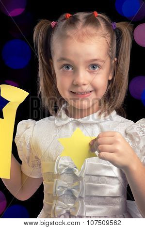 Little Girl Happy Cutting Paper Figures For Christmas Against Black Background With Blurred Lights