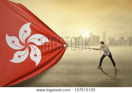 Asian Person Pulling Flag Of Hongkong