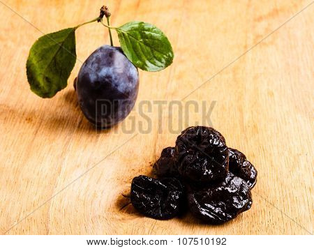 Dried Plums And Fresh Prune Fruit On Wooden Table