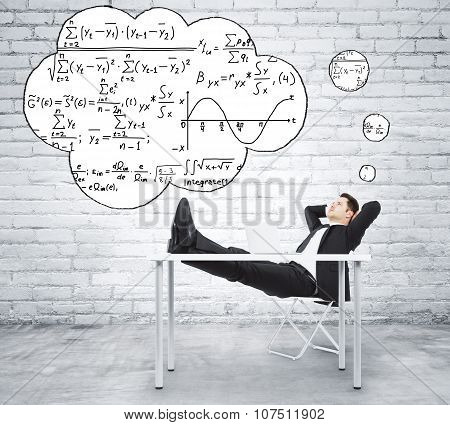 Businessman Sitting At The Table And Thinking About Solution Of The Equation