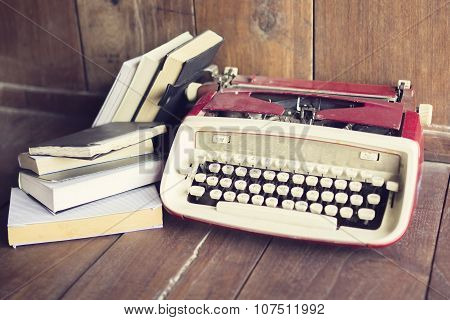 Old Style Typewriter With Book On Wooden Floor