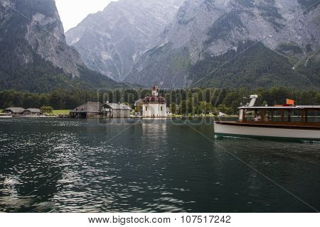 KOENIGSSEE, GERMANY - AUGUST 13, 2015: Boat on the Koenigssee near Berchtesgaden in Bavaria with the Church of St. Bartholomew