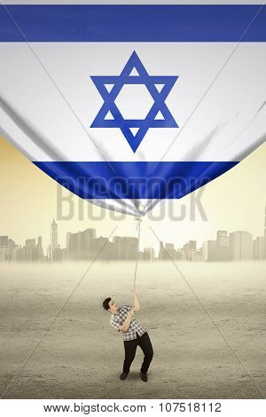 Man Pulling Down Israel National Flag